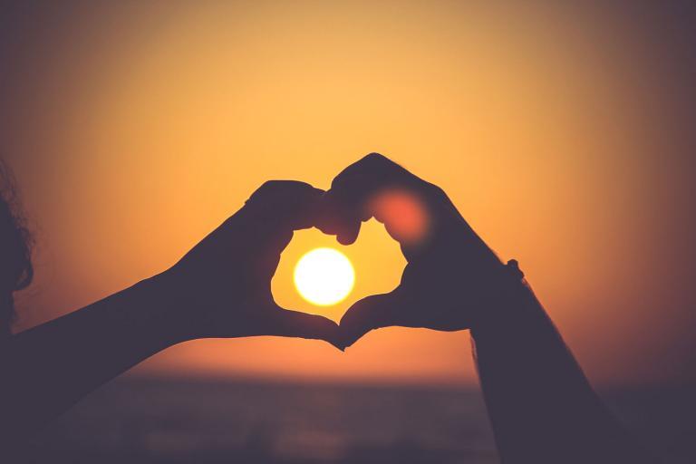 Mains formant un coeur sur fond de soleil couchant